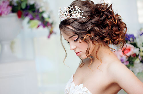 A close-up shot of a bride with a tiara in her curly hair