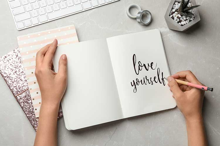 "woman writing ""love yourself"" in a journal"